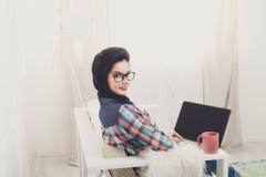 Ung flicka på den vita soffan med en bärbar dator Arkivfoto
