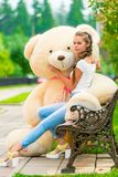 Ung flicka på en bänk med en favorit- nallebjörn royaltyfri foto