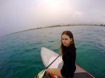 Ung flicka på en ställning upp surfingbrädan i Hawaii royaltyfri bild
