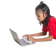 Ung flicka på golvet med bärbar dator I Royaltyfri Foto
