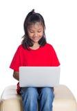 Ung flicka på soffan med bärbar dator I Arkivbilder