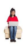 Ung flicka på soffan med bärbar datordropp Arkivbild