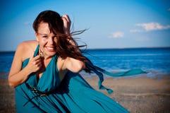 Ung flicka på stranden i härlig lång klänning Fotografering för Bildbyråer