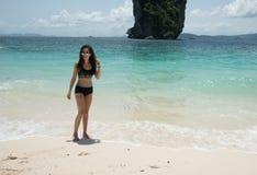 Ung flicka på stranden i svart baddräkt fotografering för bildbyråer