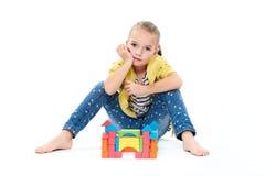 Ung flicka på uppförandeterapi som bygger en slott med träleksakkvarteret Begrepp för terapi för barnlek på vit bakgrund royaltyfria foton