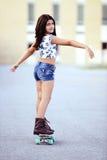 Ung flicka på ett skridskobräde Arkivfoton