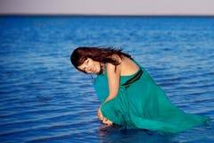 Ung flicka på stranden i härlig lång klänning Arkivbilder