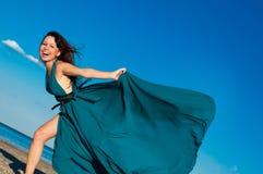 Ung flicka på stranden i härlig lång klänning Royaltyfri Fotografi