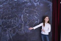 Ung flicka plattforer på blackboarden Arkivbilder