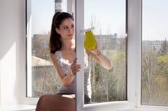 Flickan sitter på en fönstersill och tvättar ett fönster Arkivbild