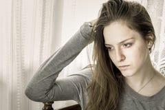 Ung flicka som är ledsen hemma med en hand på hennes huvud som bort ser royaltyfri bild