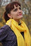 ung flicka som är rödhårig i en gul halsduk Arkivbild
