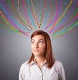 Ung flicka som är tänkande med den färgrika abstrakt begrepp, fodrar uppe i luften Royaltyfri Foto
