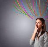 Ung flicka som är tänkande med den färgrika abstrakt begrepp, fodrar uppe i luften Arkivfoton