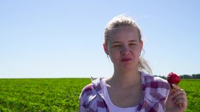 Ung flicka som äter den röda nya jordgubben på fältet lager videofilmer
