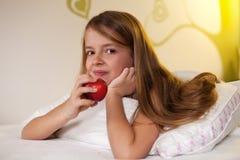 Ung flicka som äter ett äpple i säng Arkivbild