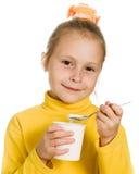 Ung flicka som äter yoghurt Arkivbild