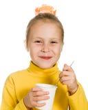 Ung flicka som äter yoghurt Royaltyfria Foton