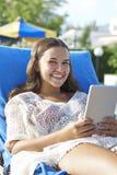 Ung flicka som använder den digitala minnestavlan Arkivfoton