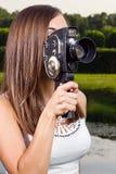 Ung flicka som använder en gammal kamera royaltyfri bild
