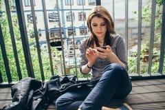 Ung flicka som använder en Smartphone på en balkong Arkivbilder