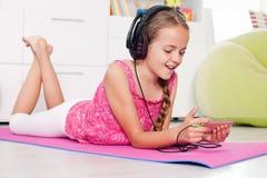 Ung flicka som använder hennes telefon som lyssnar till musik Arkivfoto