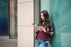 Ung flicka som använder minnestavlan i gatan, hipsterstil, utomhus- stående, lycklig framsida royaltyfri fotografi