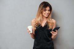 Ung flicka som använder mobiltelefon- och innehavkoppen kaffe Arkivbild
