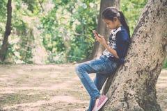 Ung flicka som använder mobiltelefonen under stort träd Royaltyfri Bild