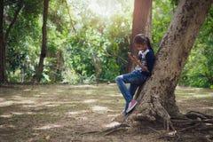 Ung flicka som använder mobiltelefonen under stort träd Royaltyfria Foton