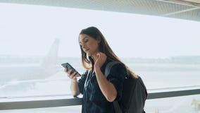 Ung flicka som använder smartphonen nära flygplatsfönster Den lyckliga europeiska kvinnan med ryggsäcken använder mobilen app i t