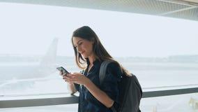 Ung flicka som använder smartphonen nära flygplatsfönster Den lyckliga europeiska kvinnan med ryggsäcken använder mobilen app i t fotografering för bildbyråer