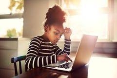 Ung flicka som arbetar på hennes läxa Arkivbild