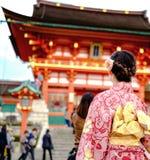 Ung flicka som bär den japanska kimonot som framme står av japan Arkivfoto
