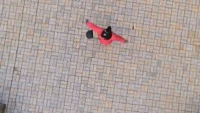 Ung flicka som bär röda omslagscirklar på jordningen som skjuter från surret arkivfilmer