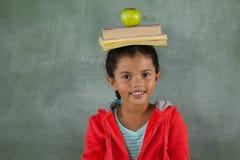 Ung flicka som balanserar böcker och äpplet på hennes huvud Arkivfoton