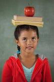 Ung flicka som balanserar böcker och äpplet på hennes huvud Royaltyfri Bild