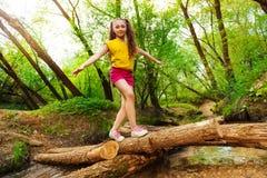 Ung flicka som balanserar på en journal som korsar över floden Royaltyfria Foton