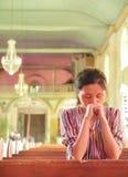Ung flicka som ber i kyrka Arkivbild