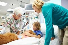 Ung flicka som besökas i sjukhus av terapihunden Arkivbild