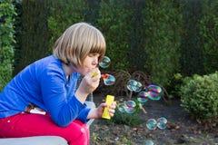 Ung flicka som blåser bubblor från såplödder Arkivfoto