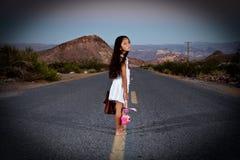 Ung flicka som bort heading ner huvudvägen som är rinnande. Fotografering för Bildbyråer