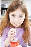 Ung flicka som dricker canen av sodavatten till och med sugrör arkivfoto