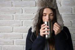 Ung flicka som dricker en varm drink slitage vit vinter för härlig stående för begreppsklänningflicka Arkivbilder