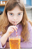 Ung flicka som dricker exponeringsglas av sodavatten till och med sugrör royaltyfria foton