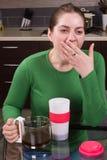 Ung flicka som dricker kaffe i kök Arkivfoto