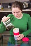 Ung flicka som dricker kaffe i kök Fotografering för Bildbyråer