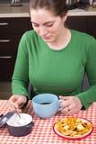 Ung flicka som dricker kaffe i kök Royaltyfria Foton