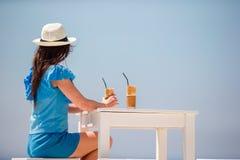Ung flicka som dricker kallt kaffe som tycker om havssikt Den härliga kvinnan kopplar av under exotisk semester på stranden som t Royaltyfri Foto