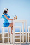Ung flicka som dricker kallt kaffe som tycker om havssikt Den härliga kvinnan kopplar av under exotisk semester på stranden som t Fotografering för Bildbyråer